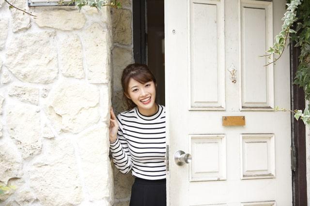 玄関から挨拶をする女性